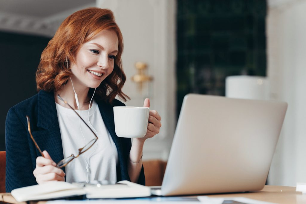Intelligent female student has online course, concentrated in screen of laptop computer, learns foreign languages distantly, drinks tea or coffee, poses at desktop. Woman worker has video conference (Intelligent female student has online course, conce